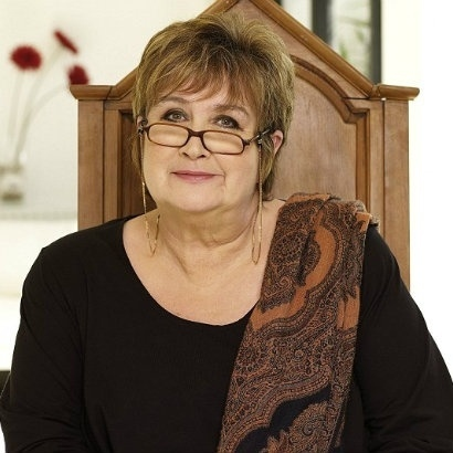 Image of Jenni Murray sat in chair with brown scarf over one shoulder