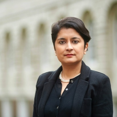 Image of Shami Chakrabarti standing in front of a large white building