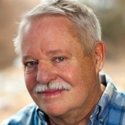 Image of Armistead Maupin in a grey tweed jacket, smiling to camera