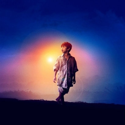 Actor who is a young boy alone with sun behind him