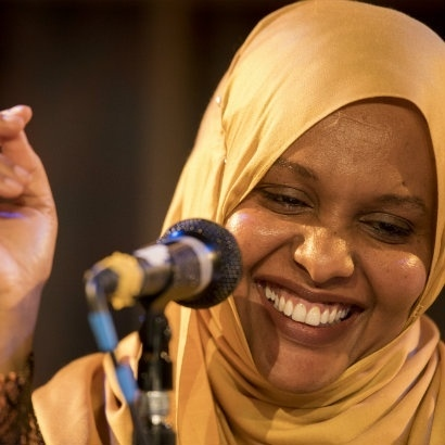 Image of Asha Lul Mohamud Yusuf wearing a yellow headscarf and laughing in front of a microphone