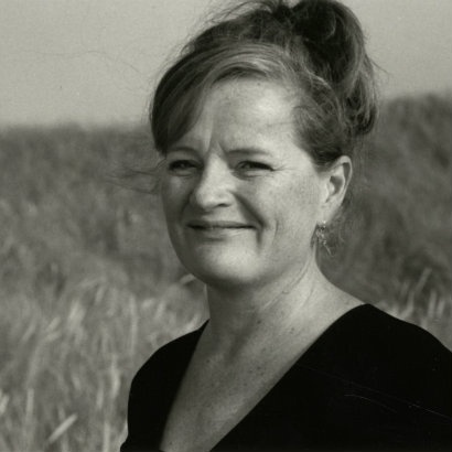 Black and white image of Dorthe Nors in a wheatfield, smiling at the camera