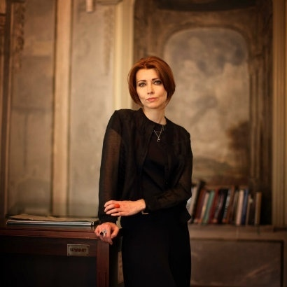 Image of Elif Shafak leaning against a wooden cabinet in an old stone building
