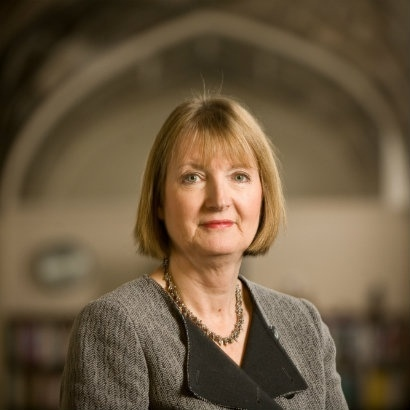 Image of Harriet Harman in a smart grey jacket with a black collar, standing in a large library