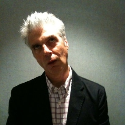 Picture of Jon Savage stood under a spotlight, rolling his eyes up at the ceiling