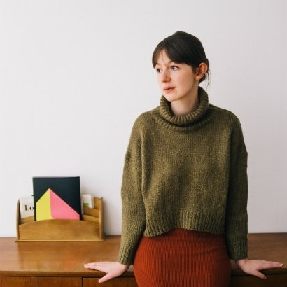 Image of Sally Rooney sitting on the edge of a desk, wearing a green woollen jumper and orange skirt