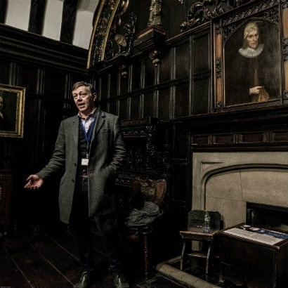 Picture of tour guide Jonathan Schofield delivering one of her tours in a dark, wood-panelled room