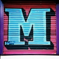 Picture of a large M in graffiti on a shop shutter in Manchester