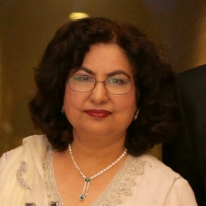 Qaisra Shahraz in white linen top and pearl necklace