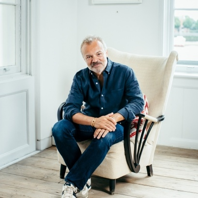 Author Graham Norton smiling and looking relaxed in a comfy armchair