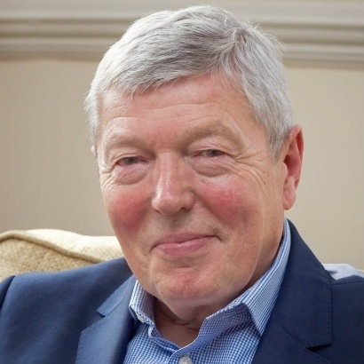 Image of a smiling Alan Johnson in a blue suit and shirt