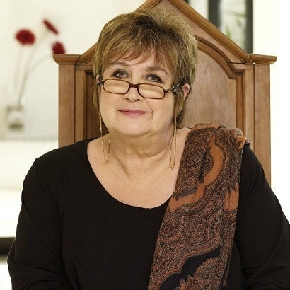 Headshot of Jenni Murray, sitting in a wooden, high-backed chair