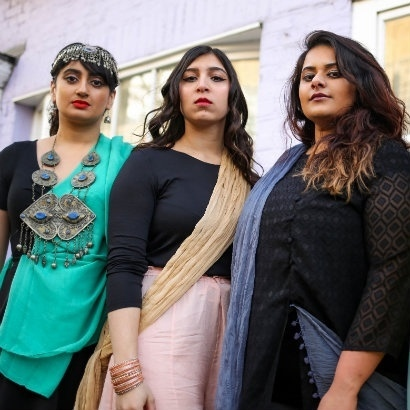Group photo spoken word poets, collectively known as The Yoniverse, Amani Saeed, Shagufta Iqbal and Afshan D'Souza-Lodhi, standing next to each other outside