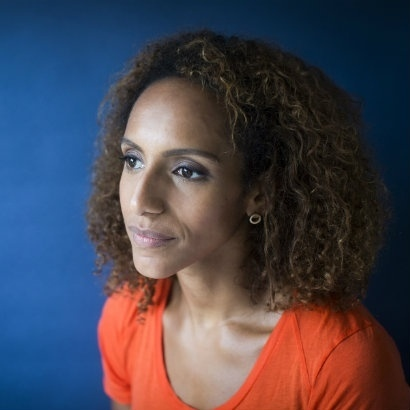 Head and shoulders image of Afua Hirsch wearing an orange top against a bright blue background