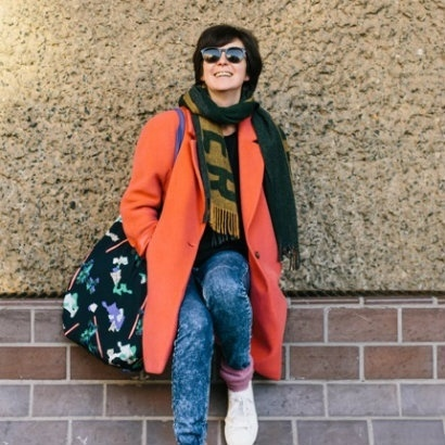 Photo of author Olivia Laing, wearing a bright orange coat and sunglasses and leaning on a wall with one foot resting on the wall