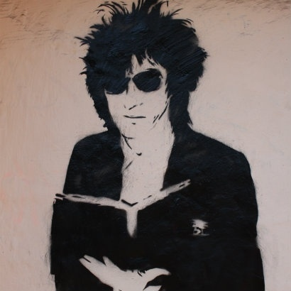 Black and white Banksy-style graffiti image of John Cooper Clark reading a book