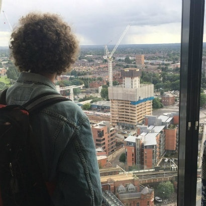 Shot taken from behind a young person looking out the window over the skyline of Manchester