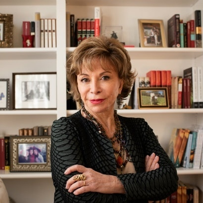 Head and shoulders shot of author Isabel Allende in front of bookcases