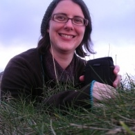 A picture of MLF Children and Young People's Coordinator Liz Postlethwaite sitting in a field, smiling, wearing headphones