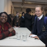 A picture of Malorie Blackman sitting at a table during a book signing talking to a young fan